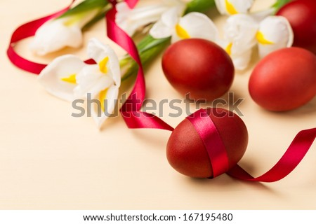 Easter eggs, white flowers and red ribbon on the beige table - stock photo