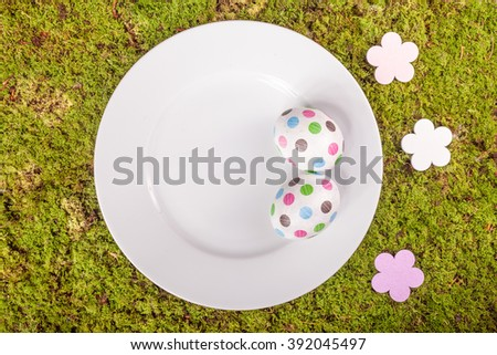 Easter eggs, white plate and decoration on green moss background