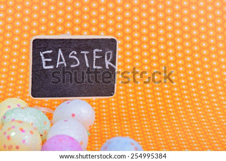Easter eggs with blackboard with copy-space over orange floral background - stock photo