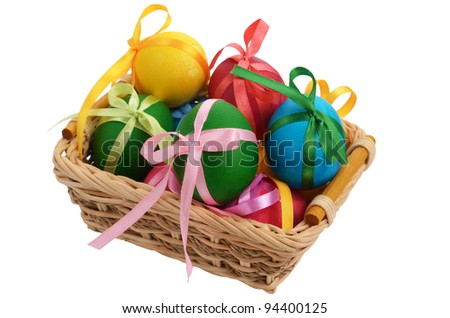 Easter eggs with bows in the basket over white background