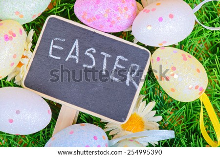 Easter eggs with chalkboard on the grass with copy-space - stock photo