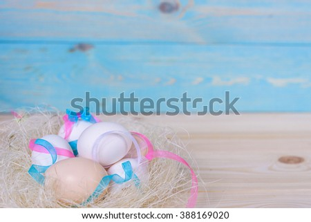 Easter eggs with colourfulll tapes and bow in nest over blue wood background. Top view with tag for copy space - stock photo