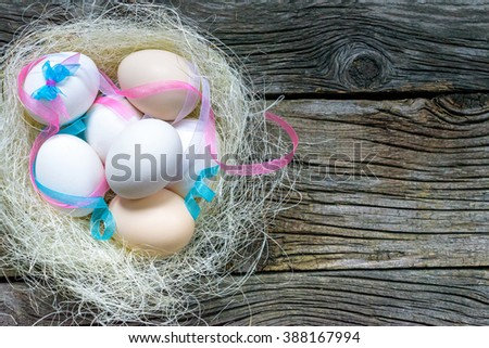 Easter eggs with colourfulll tapes and bow in nest over old wood. Top view with tag for copy space - stock photo