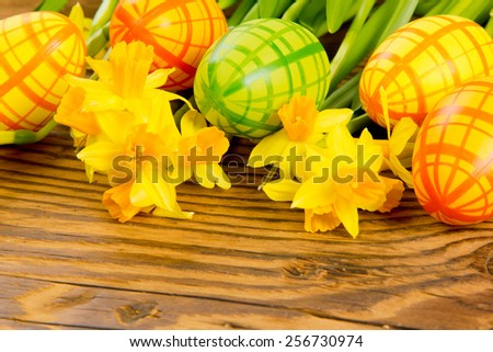 Easter eggs with daffodil blooms on wooden board - stock photo