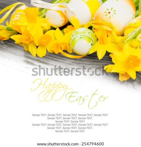Easter eggs with daffodil blooms on wooden board with white sapce for text - stock photo