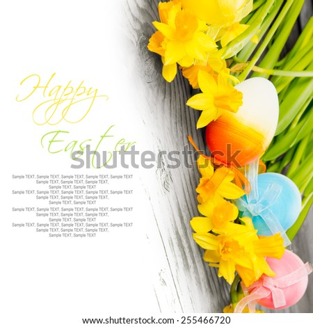 Easter eggs with daffodil blooms on wooden board with white space for text - stock photo