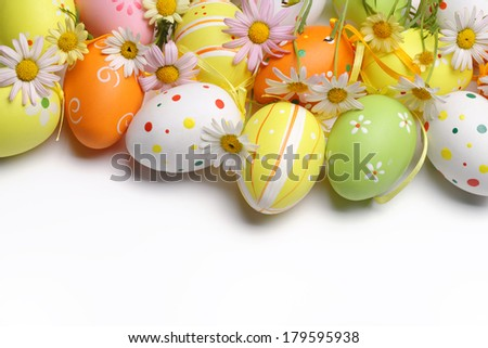 Easter eggs with daisy flower on white background - stock photo