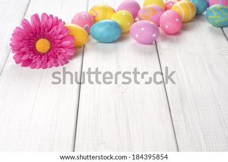 Easter Eggs with Daisy in a row at top of frame on white board background with room or space for copy, text.  Horizontal - stock photo