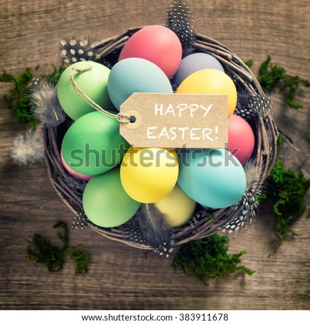 Easter eggs with feather decoration and tag on wooden background. Vintage style toned picture - stock photo