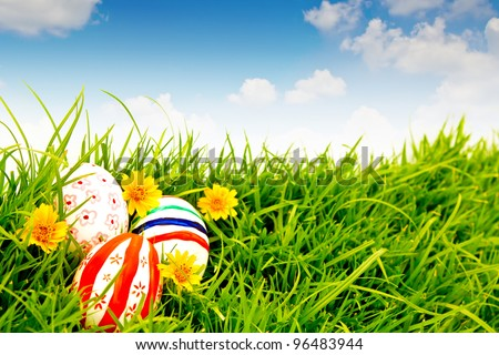 Easter Eggs with flower on Fresh Green Grass over blue sky