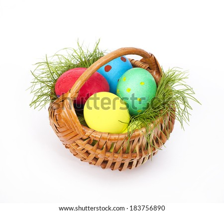 Easter eggs  with grass in wicker on white background - stock photo