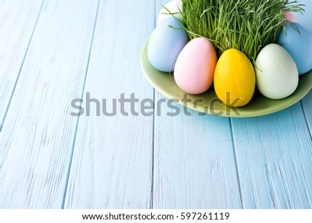 Easter Eggs With Grass Served On The Plate On A Blue Background, Copy Space
