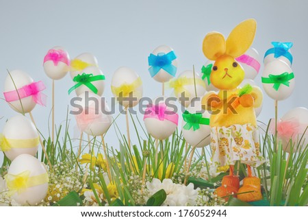 Easter eggs with multicolored ribbons on wooden sticks and green grass with rabbit