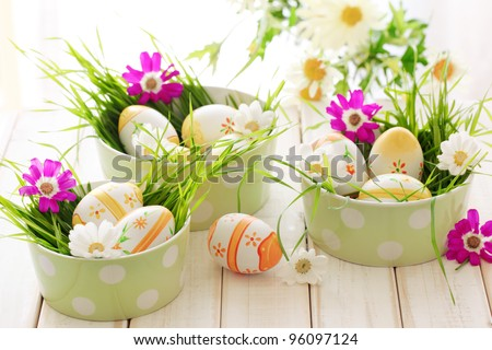 Easter eggs with spring flowers on table. - stock photo