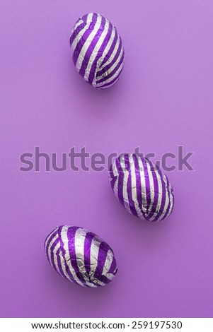 easter eggs with stripes, on a plain purple background, with shadows for authentic, natural light look - stock photo