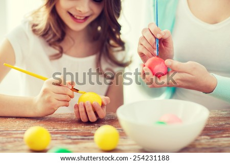 easter, family, holiday and child concept - close up of little girl and mother coloring eggs for easter - stock photo