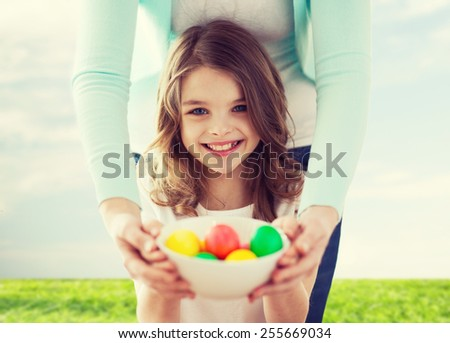 easter, family, holiday and child concept - smiling little girl and mother holding bowl with colored eggs - stock photo