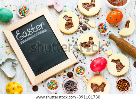 Easter festive baking background homemade cookies for child in the form of bunny, beautiful eggs, colorful sprinkling, chocolate on a white background. Empty space for text top view - stock photo