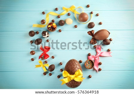 Easter frame with chocolate sweets on color wooden background