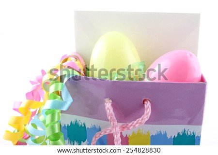 Easter gift bag with eggs, card, and ribbon. - stock photo