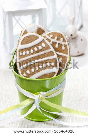 Easter gingerbread cookies in green bucket on wooden table. - stock photo