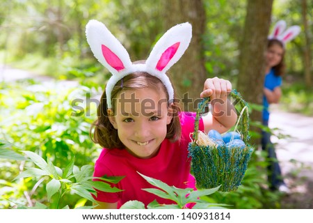 Easter girl with eggs basket and funny bunny face expression at the forest - stock photo