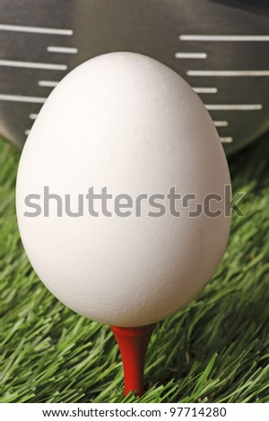 Easter golf. An egg on a red golf  tee in the green grass with the head of a driver  behind the egg. - stock photo