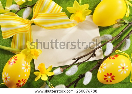 Easter greeting card with copy space, yellow easter eggs, narcissus and pussy willow on tablecloth - stock photo
