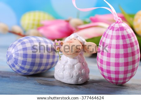 easter greeting card with cute lamb figurine and eggs on blue wooden table  - stock photo
