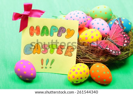 Easter greeting card with eggs in nest on green background - stock photo