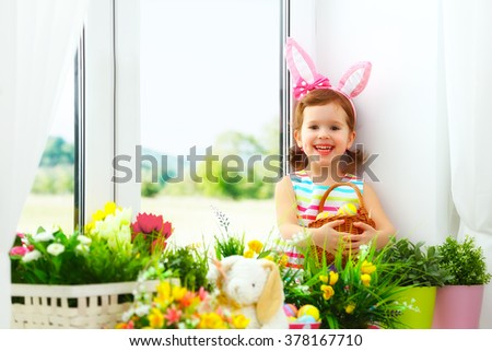 Easter. happy baby girl with bunny ears and colorful eggs sitting at the window of a house in flowers
