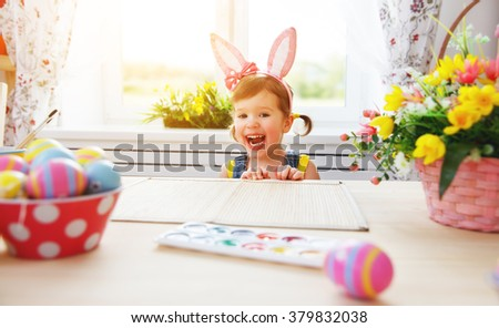 Easter. happy child girl with bunny ears decorates the home for Easter colored eggs and flowers