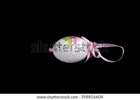 Easter hen's egg with carving. Egg arranged on a black background. - stock photo