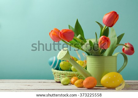 Easter holiday with tulip flowers and egg decorations in basket - stock photo