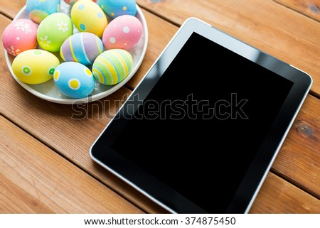 easter, holidays, technology, advertisement and object concept - close up of colored easter eggs on plate and blank tablet pc computer - stock photo