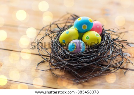 easter, holidays, tradition and object concept - close up of colored easter eggs in nest on wooden surface - stock photo