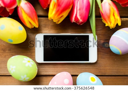 easter, holidays, tradition and object concept - close up of colored easter eggs, tulip flowers and smartphone with blank screen on wooden surface - stock photo