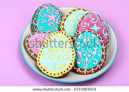 Easter homemade baked gingerbread cookies in the form of eggs with different pattern of icing on plate. Studio Photo