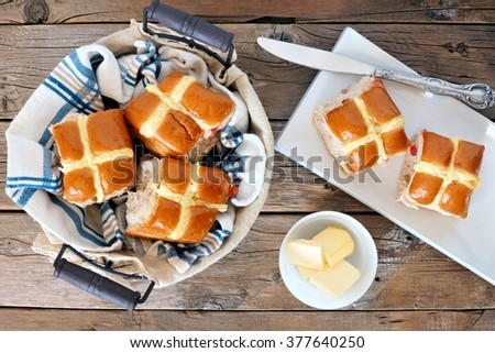 Easter Hot Cross Buns, overhead scene with basket and plate on rustic wood background - stock photo