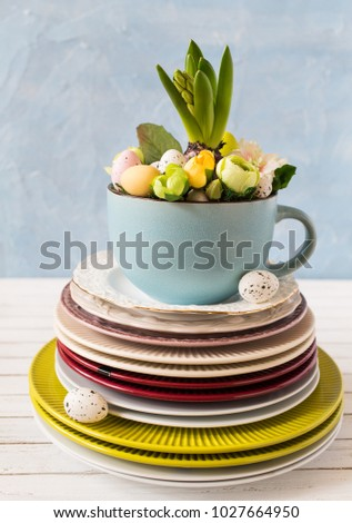 Easter hyacinth comrosition in mug on a stack of plates.