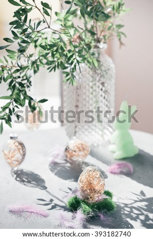 Easter interior with glass egg decorations, green leaves branch, feathers and bunny candle beside window. Natural light photo. Modern simple decoration style concept. Toned photo.  - stock photo