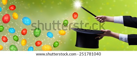 Easter magic for copy space - magician hands with black hat and wand - stock photo