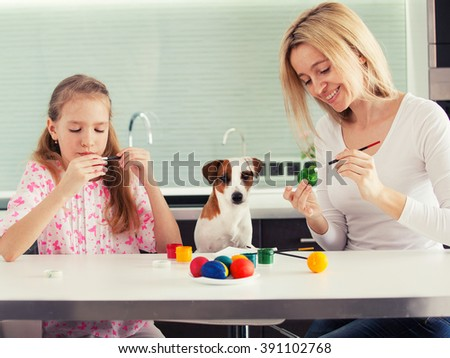 Easter. Mother and child painting eggs - stock photo
