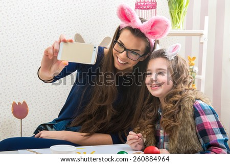 Easter - Mother and daughter with bunny ears, made Selfie photo - stock photo