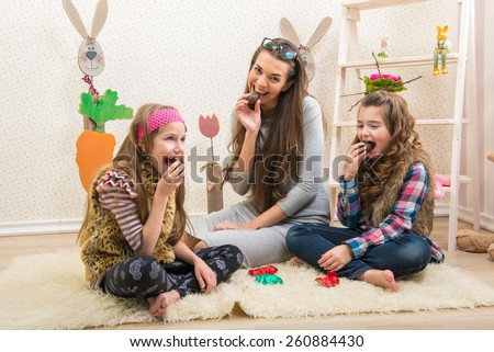 Easter - Mother and two daughters eat chocolate eggs - stock photo