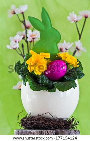 easter motif, ostrich egg, easter bunny, cherry blossom, easter nest, green background - stock photo
