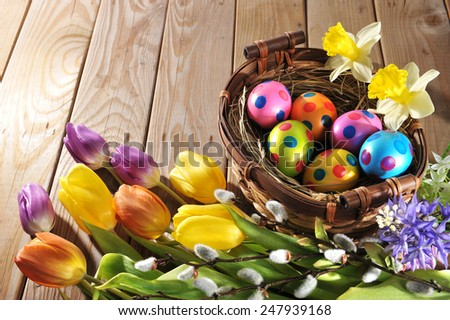 Easter nest with colored hen�s eggs, narcissus, hyacinth and pussy willow on wooden board - stock photo