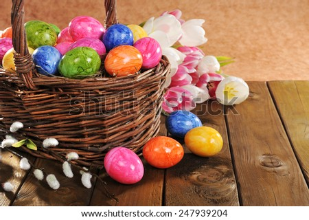 Easter nest with colored hen�s eggs, tulip and pussy willow on old wooden board - stock photo