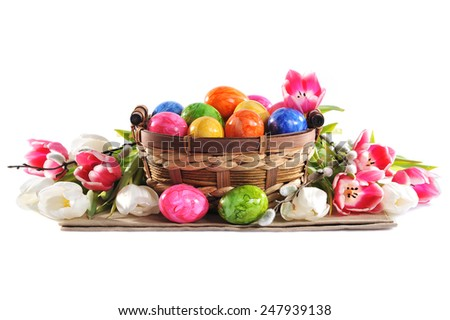 Easter nest with colored hen�s eggs, tulip and pussy willow on white background - stock photo