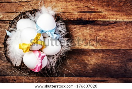 Easter nest with Eggs,  ribbons and white feathers on wooden background with copy space for text in rustic  style, close up and top view.